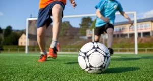 21260315 - little boys playing football on field