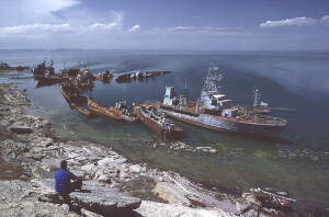 BAKU, AZERBAIJAN - MAY 1997: A man on the shore over-looks the view of abandoned Soviet-era warships on Nargin Island in Baku Bay in the Caspian Sea on May, 1997 in Baku, Azerbaijan. (Photo by Reza/Getty Images)